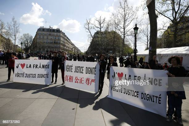 People stand behind banners reading 'I love France truth justice dignity' as they take part in a demonstration on the Place de la Republique in Paris...
