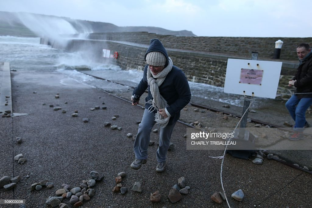 People stand behind barriers as waves break in the harbour of Auderville, northwestern France, on February 8, 2016, as strong winds hit the region. Winds of over 130 kh/h were recorded in the region where 16 departments have been placed under alert for wind and flooding waves. / AFP / CHARLY TRIBALLEAU