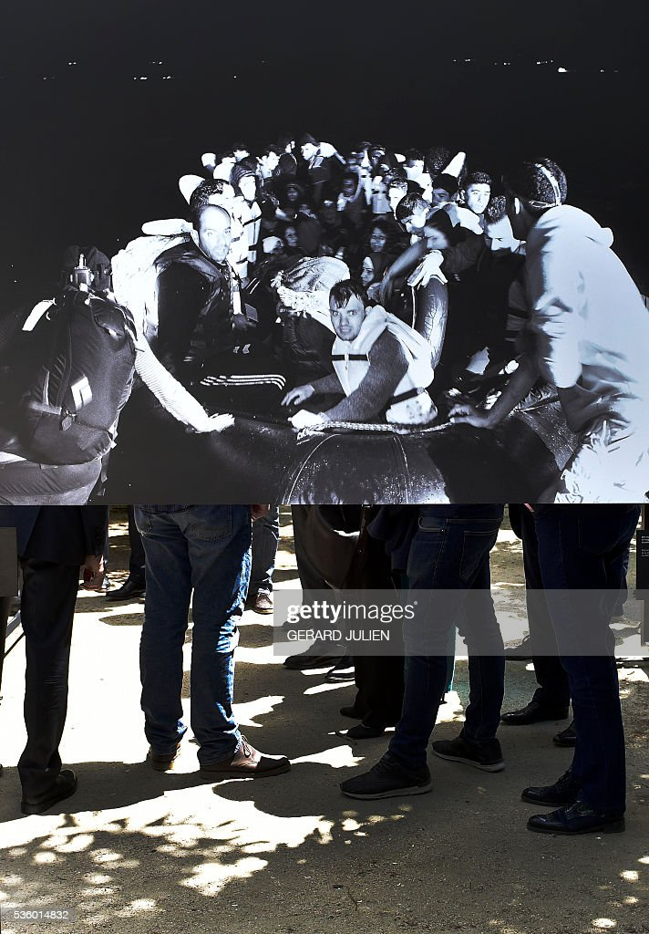 People stand behind photos by French photographer Pierre Marsaut during the opening of the exhibition 'Caminos de Exilio' ('Ways of Exile') at Retiro Park in Madrid, on 31 May 2016. The exhibition shows pictures of refugees taken by five photographers; Sima Diab (Syria), Giorgios Moutafis (Greece), Manu Brabo (Spain), Olivier Jobard (France) and Pierre Marsaut (France) and has been organized by the French Embassy and the French Institute in Spain, on the sidelines photo festival of PhotoEspana 2016. / AFP / GERARD