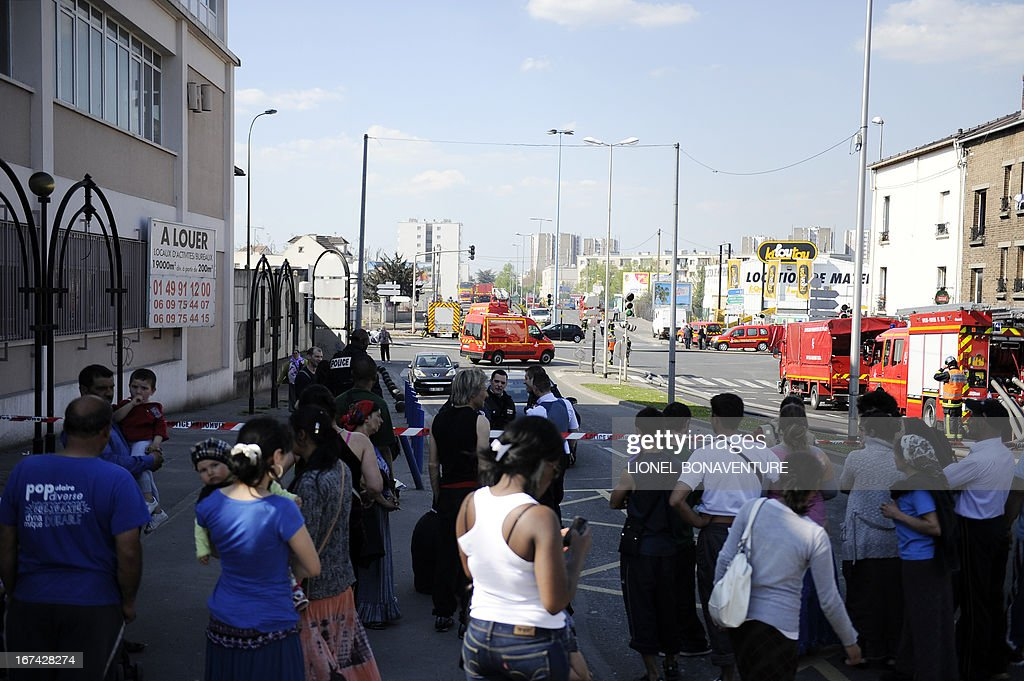 People stand behind police barriers on April 25, 2013 in the Paris' suburb of Bobigny, after some 250 people from the Roma community were evacuated as a large fire caught in a nearby factory spread in their camp.