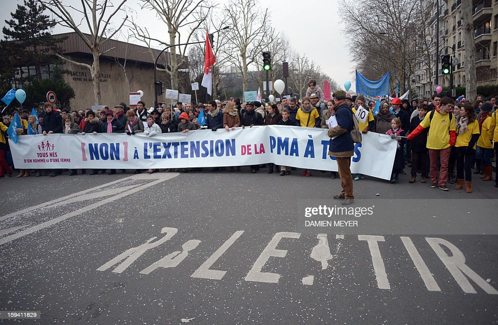 People stand beside a banner reading in French 'No to the extension of the medically assisted procreation (PMA) for all' as they take part in a protest against same-sex marriage on January 13, 2013 in Paris. Tens of thousands march in Paris on January 13 to denounce government plans to legalise same-sex marriage and adoption which have angered many Catholics and Muslims, France's two main faiths, as well as the right-wing opposition. The French parliament is to debate the bill -- one of the key electoral pledges of Socialist President -- at the end of this month. AFP PHOTO / DAMIEN MEYER