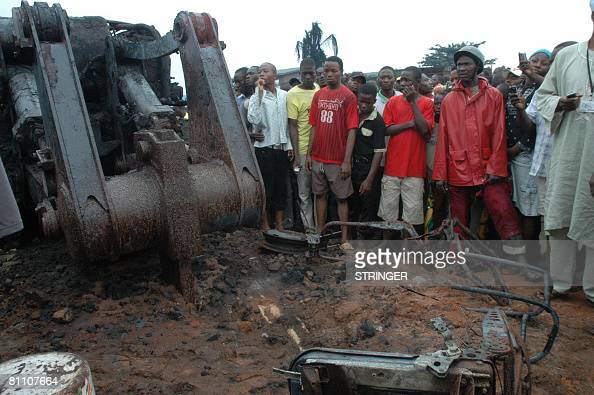 People stand beside a burnt piece of earthmoving equipment on May 16 2008 in a northern suburb of Lagos following an explosion on May 15 on an oil...
