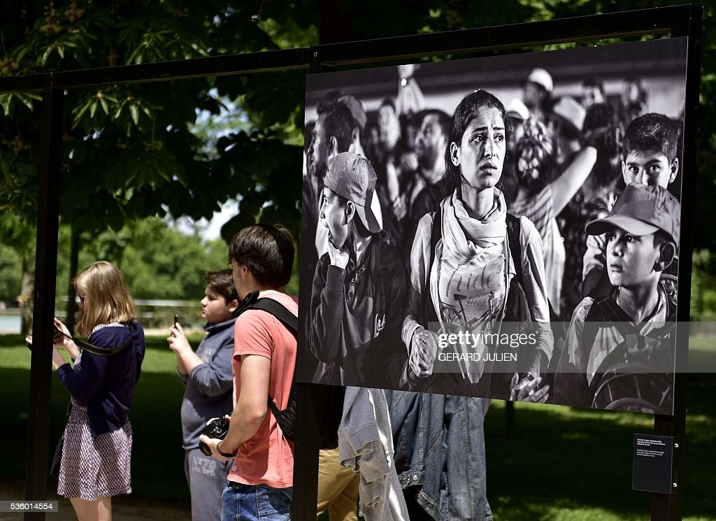 People stand beside a photo by Syrian photographer Sima Diab during the opening of the exhibition 'Caminos de Exilio' ('Ways of Exile') at Retiro Park in Madrid, on 31 May 2016. The exhibition shows pictures of refugees taken by five photographers; Sima Diab (Syria), Giorgios Moutafis (Greece), Manu Brabo (Spain), Olivier Jobard (France) and Pierre Marsaut (France) and has been organized by the French Embassy and the French Institute in Spain, on the sidelines photo festival of PhotoEspana 2016. / AFP / GERARD