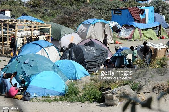 People stand beside tents in the site dubbed 'New Jungle' where migrants trying to cross the Channel to reach Britain have camped out around the...