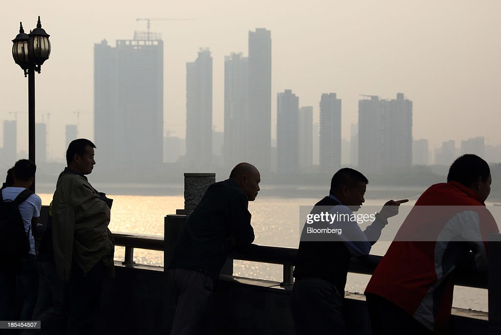 People stand beside the Chang Jiang river as residential buildings stand in the background in Wuhan, China, on Sunday, Oct. 20, 2013. China's economic expansion accelerated to 7.8 percent in the third quarter from a year earlier, the statistics bureau said Oct. 18, reversing a slowdown that put the government at risk of missing its 7.5 percent growth target for 2013. Photographer: Tomohiro Ohsumi/Bloomberg via Getty Images
