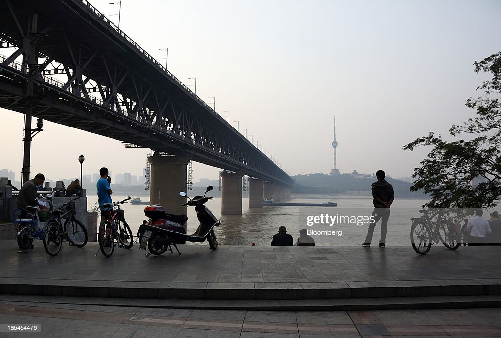 People stand beside the Chang Jiang river in Wuhan, China, on Sunday, Oct. 20, 2013. China's economic expansion accelerated to 7.8 percent in the third quarter from a year earlier, the statistics bureau said Oct. 18, reversing a slowdown that put the government at risk of missing its 7.5 percent growth target for 2013. Photographer: Tomohiro Ohsumi/Bloomberg via Getty Images