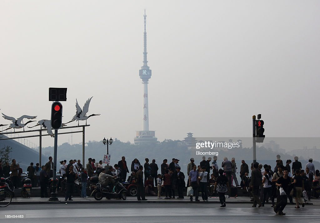 People stand beside the Chang Jiang river with the television tower, center, in the background in Wuhan, China, on Sunday, Oct. 20, 2013. China's economic expansion accelerated to 7.8 percent in the third quarter from a year earlier, the statistics bureau said Oct. 18, reversing a slowdown that put the government at risk of missing its 7.5 percent growth target for 2013. Photographer: Tomohiro Ohsumi/Bloomberg via Getty Images