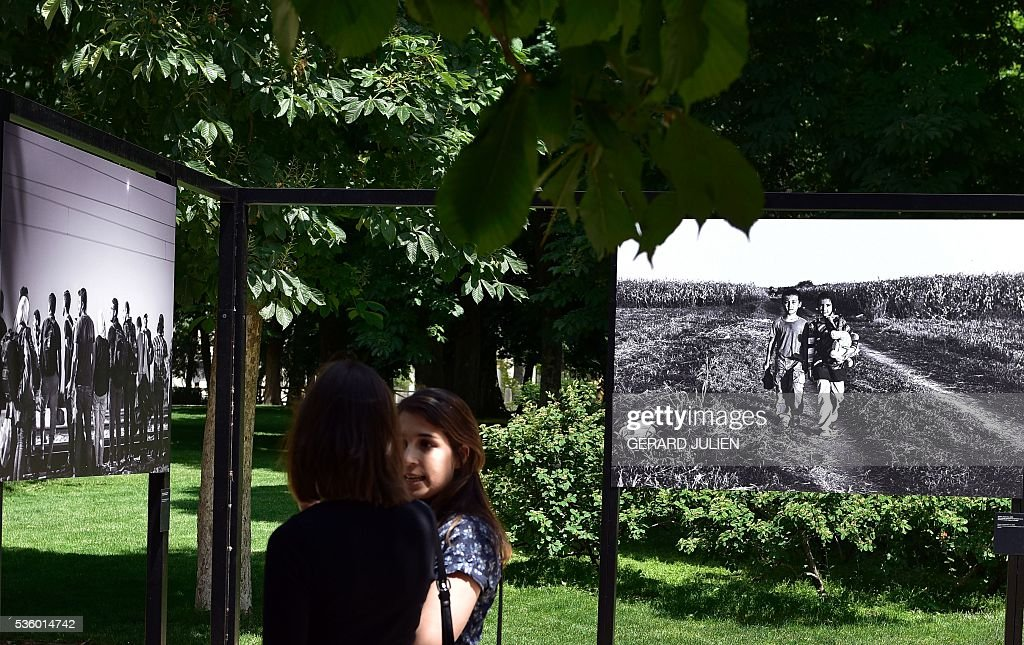 People stand between photos by Syrian photographer Sima Diab during the opening of the exhibition 'Caminos de Exilio' ('Ways of Exile') at Retiro Park in Madrid, on 31 May 2016. The exhibition shows pictures of refugees taken by five photographers; Sima Diab (Syria), Giorgios Moutafis (Greece), Manu Brabo (Spain), Olivier Jobard (France) and Pierre Marsaut (France) and has been organized by the French Embassy and the French Institute in Spain, on the sidelines photo festival of PhotoEspana 2016. / AFP / GERARD