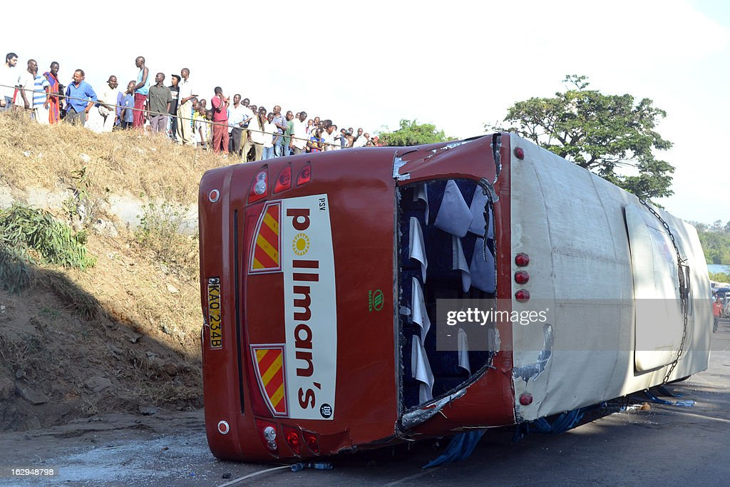People stand by a bus after it veered off the road and capsized as it with heading to the Moi international airport in Mombasa early on March 2, 2013. Six of the 15 tourists on board were injured and taken to the hospital. AFP PHOTO / STR