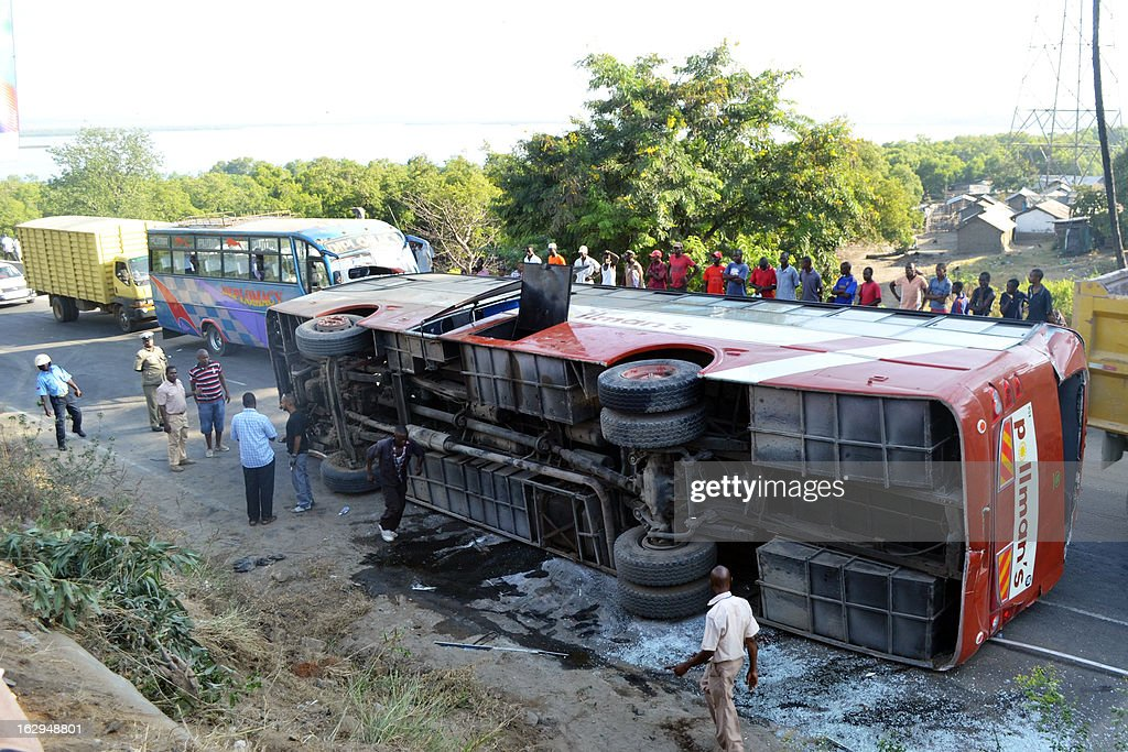 People stand by a bus after it veered off the road and capsized as it with heading to the Moi international airport in Mombasa early on March 2, 2013. Six of the 15 tourists on board were injured and taken to the hospital.