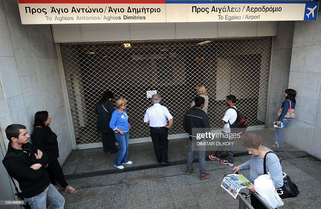 People stand by a closed underground station entrance in the center of Athens on May 5, 2010. A nationwide general strike gripped Greece in the first major test of the socialist government's resolve to push through unprecedented austerity cuts needed to avert fiscal meltdown.