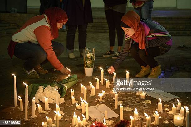 People stand by as a makeshift memorial is made after vigil at the University of North Carolina following the murders of three Muslim students on...