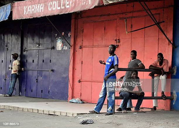 People stand by closed stores on January 18 2011 in the proOuattara popular district of Adjame in Abidjan as supporters of internationally recognized...