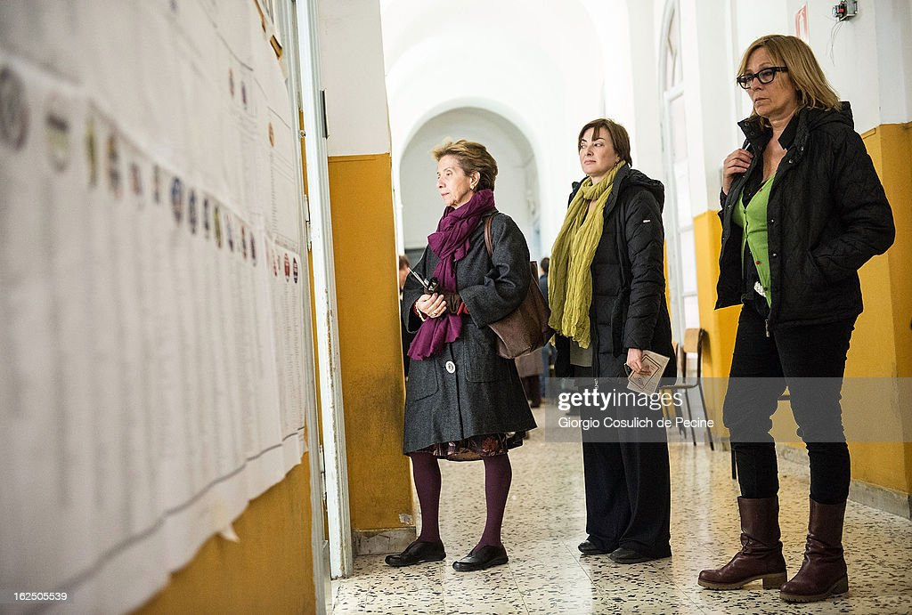 People stand by electoral banners at a polling station on February 24, 2013 in Rome, Italy. Italians are heading to the polls today to vote in the elections, as the country remains in the grip of economic problems . Pier Luigi Bersani's centre-left alliance is believed to be a few points ahead of the centre-right bloc led by ex-Prime Minister Silvio Berlusconi.
