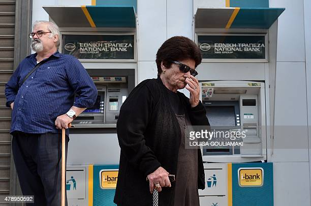 People stand by Greece national bank's empty ATM's in central Athens on June 29 2015 as Greece ordered its banks to shut for one week and imposed...
