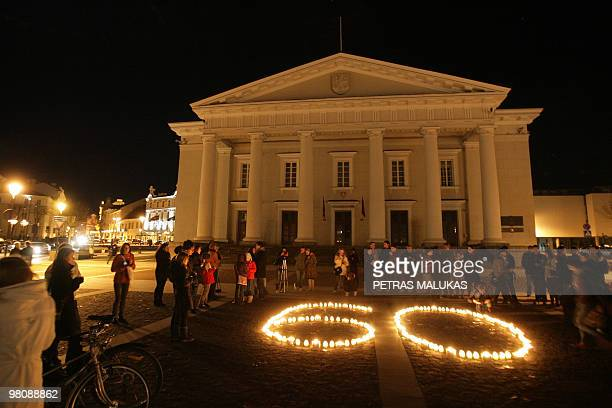 People stand by lit candles forming the number 60 in front of the Vilnius town hall after lights have been switched off for 60 minutes on March 27...
