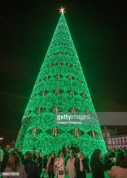 People stand by the large Christmas tree and Christmas and New Year light displays in Praca do Comercio on December 9 2017 in Lisbon Portugal The...