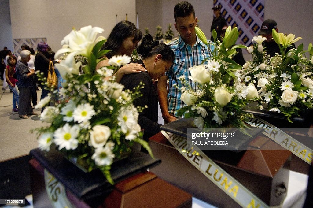 People stand by the urn with the remains of their relative who was disappeared during the Colombian civil war until recently, on June 21, 2013 in Medellin, Antioquia department, Colombia. In a ceremony, relatives of 36 victims received the remains of their loved ones, which were recently found in common graves due to information given by demobilized combatants of both, leftist guerrillas and right-wing paramilitary groups, in the framework of the country's peace process. AFP PHOTO/Raul ARBOLEDA
