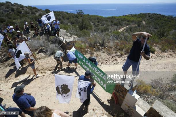 People stand closes to a sign reading 'Save our Corsican land' in front of houses built by Pierre Ferracci president of Alpha group on the...