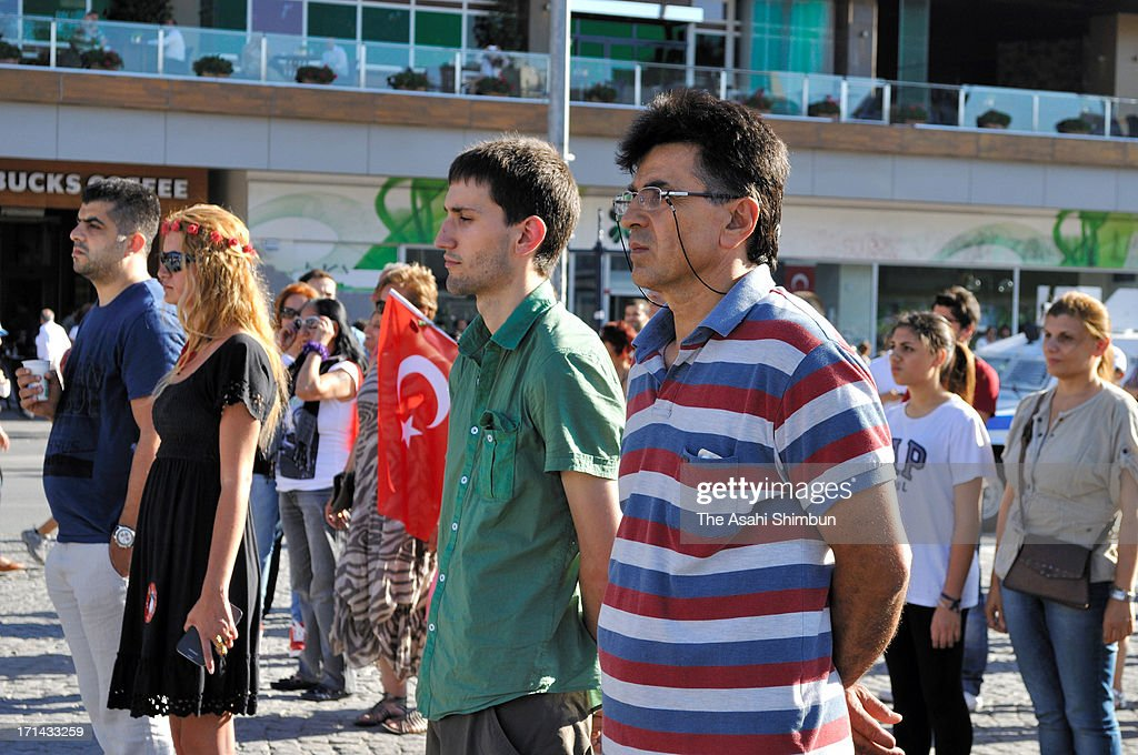 People stand during a silent protest at Taksim Square on June 22, 2013 in Istanbul, Turkey. The protest, began with performance artist Erdem Gunduz, rapidly spread to other cities.