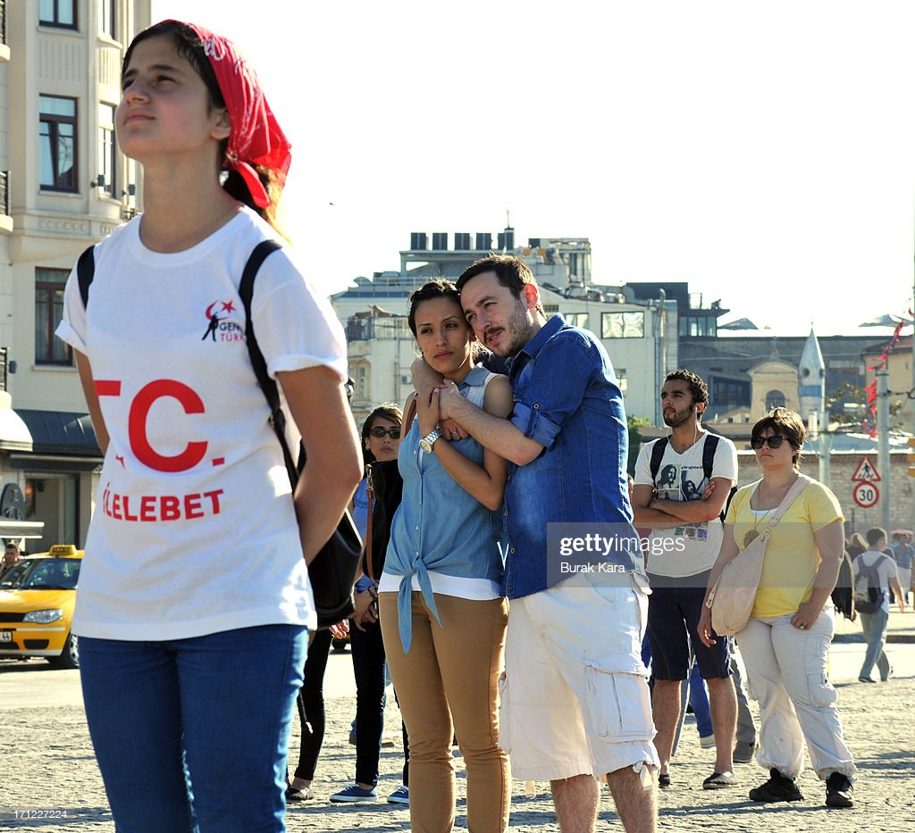 People stand during a silent protest at Taksim Square on June 23, 2013 in Istanbul, Turkey. Performance artist Erdem Gunduz, nicknamed 'The Standing Man,' became a new symbol of the anti-government protests after a eight-hour vigil in Taksim Square. Gunduz reportedly said he was protesting in solidarity with demonstrators after they were evicted from Gezi Park that adjoins Taksim Square. The protests began in May, with environmentalists upset over plans to build in Gezi Park, and has grown into a broader demonstration against Prime Minister Tayyip Erdogan's government.