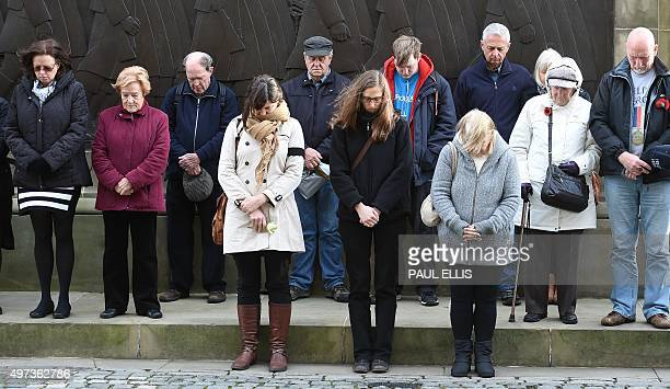 People stand for a minutes silence on the plateau at St George's Hall in Liverpool northwest England on November 16 2015 in memory of those killed in...