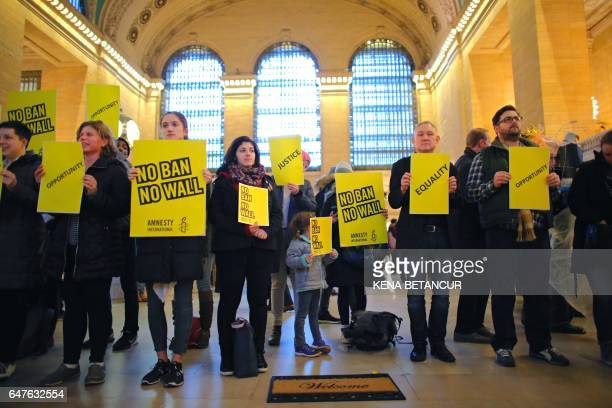 TOPSHOT People stand holding placards as they take part in a protest called 'No Ban No Wall Get Loud' hosted by Amnesty International USA inside...