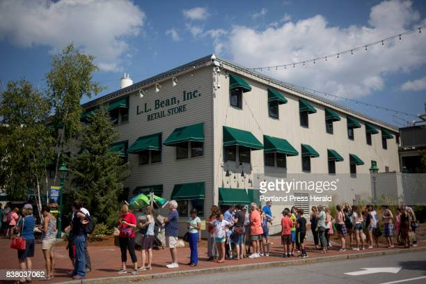 People stand in a line to look through a telescope at the partial solar eclipse at LL Bean