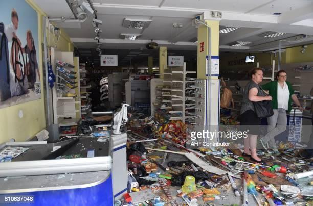 People stand in a looted Budnikowsky drugstore after riots in Hamburg's Schanzenviertel district on July 8 2017 in Hamburg northern Germany where...