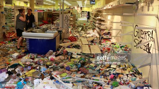 People stand in a looted Budnikowsky drugstore in Hamburg's Schanzenviertel district on July 8 2017 in Hamburg northern Germany where leaders of the...