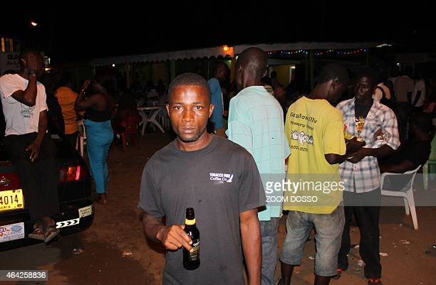 People stand in a street of Monrovia on February 22 2015 during the first night with the Ebola curfew lifted For long miserable months people have...