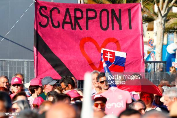 People stand in front of a banner in honor of Italian rider Michele Scarpony tragically deceased in a road accident on April 22 before the...