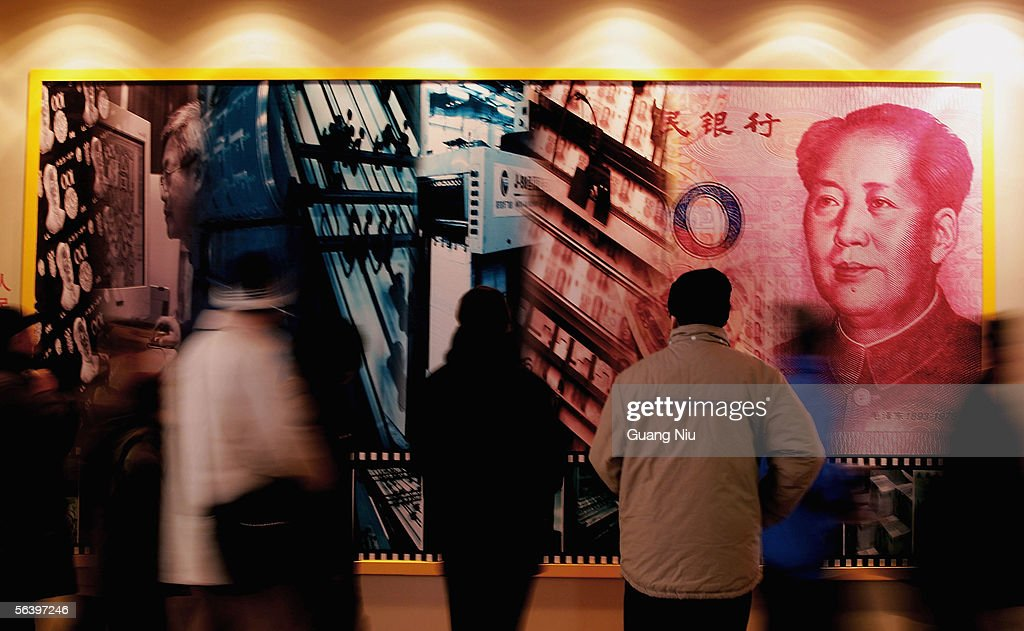 People stand in front of a billboard featuring the late chaiman Mao Zedong on a Chinese banknote at a finance exhibition held by the People's Bank of China on December 9, 2005 in Beijing, China. China's banking regulatory body says the full opening up of its banking sector will go ahead as scheduled under WTO rules, while warning the government will no longer inject fresh capital into unprofitable banks.