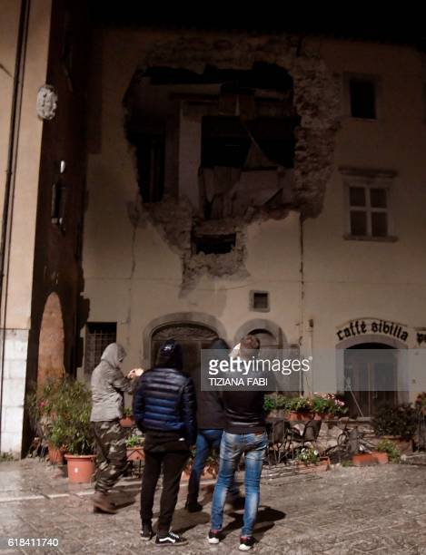 People stand in front of a destroyed building in the village of Visso central Italy after earthquakes on October 26 2016 Twin earthquakes rocked...