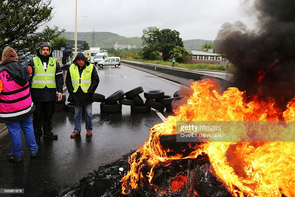 People stand in front of a fire as they block a road to protest against the government's planned labour law reforms, on May 31, 2016 in Saint-Etienne-du-Rouvray, near Rouen, northwestern France. / AFP / CHARLY