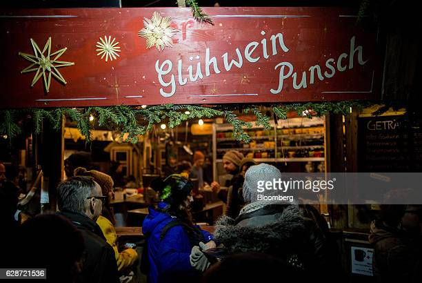 People stand in front of a gluhwein and punsch stall at a festive market in Karlsplatz square in Vienna Austria on Wednesday Dec 7 2016 The Viennese...