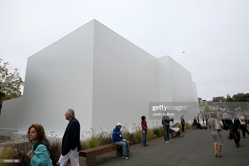 People stand in front of a large white structure built ahead of the Apple keynote at the Flint Center for the Performing Arts at De Anza College on...