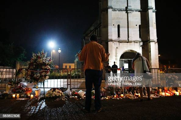 TOPSHOT People stand in front of a makeshif memorial near two gendarmes guarding the SaintEtienne du Rouvray church on July 27 after the priest...
