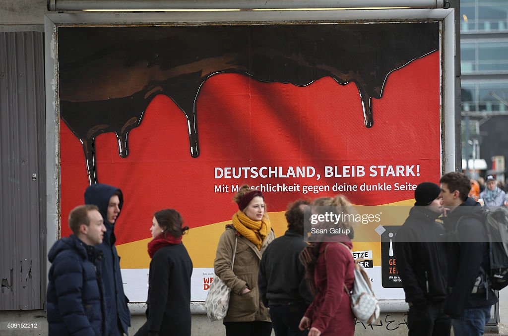 People stand in front of a poster showing the German flag with a dripping black portion and that reads: 'Germany, stay strong! With humanity against your dark side,' and below: 'Against hate and baiting, no if and but' on February 9, 2016 in Berlin, Germany. The poster is part of a campaign supported by Germany's Ministry for Families, Seniors, Women and Youth in an effort to encourage more tolerance, particularly of the 1.1 million migrants and refugees that arrived in Germany in 2015. Though a majority of Germans have shown a strong willingness to accept the newcomers and thousands have volunteered to help them, the country has also seen a growing number of attacks, including beatings, arson, vandalism and other violence against refugees and refugee shelters.