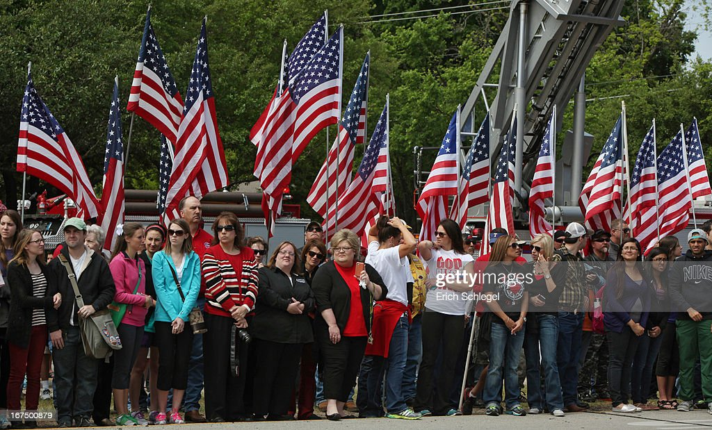 People stand in front of American flags as fire departments from around Texas pay their respects during a parade for the West Memorial Service on April 25, 2013 in Waco, Texas. The memorial service honored the volunteer firefighters that lost their lives at the fertilizer plant explosion in West, Texas last week.