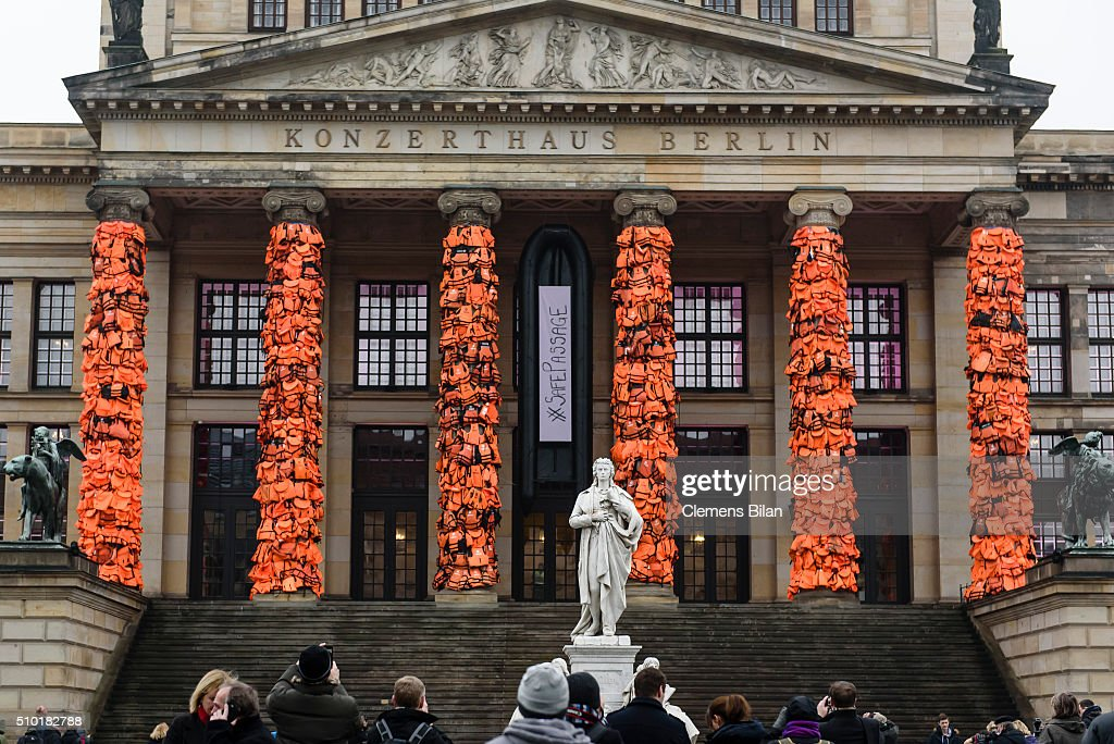 People stand in front of an art installation by Chinese artist Ai Weiwei that consists of life vests worn by refugees bound to the columns of the concert house at Gendarmenmarkt on February 14, 2016 in Berlin, Germany. The life vests were among the thousands discarded by migrants and refugees after they crossed the sea from Turkey to Greece. Ai Weiwei lives in Berlin and is currently involved in several projects relating to refugees. Up to 80,000 refugees currently live in Berlin and the city is preparing for the likely arrival of 30,000 more in 2016.