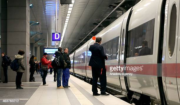 People stand in front of an ICE high speed train of the German railways company 'Deutsche Bahn' in central train station in Berlin Germany on...