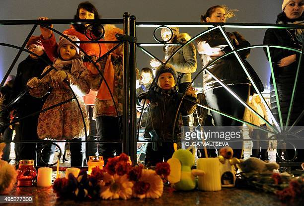 People stand in front of candles and flowers in central Saint Petersburg on November 1 in memory of the victims of a jetliner crash Flags flew at...