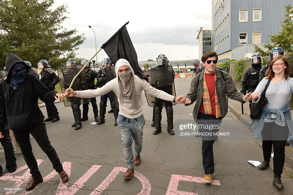 People stand in front of French riot police during a protest against the government's labour market reforms in Rennes, on May 26, 2016. The French government's labour market proposals, which are designed to make it easier for companies to hire and fire, have sparked a series of nationwide protests and strikes over the past three months.
