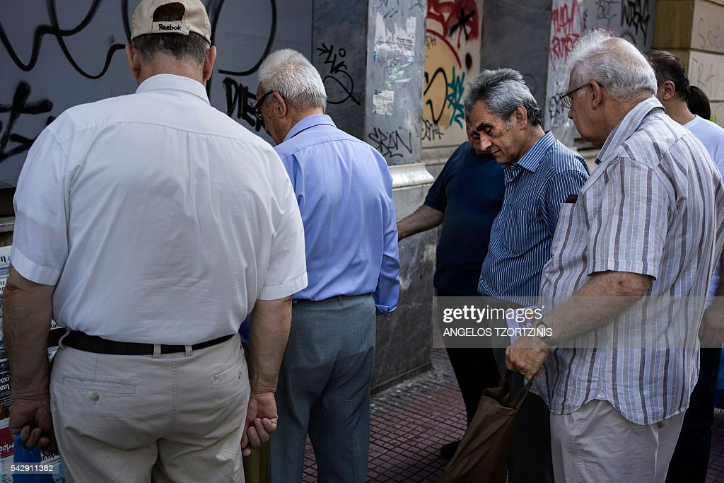 People stand in front of newspapers in Athens on June 25, 2016. The pound plunged and world stock markets slumped on June 24, 2016 after Britain's shock vote to leave the European Union, fuelling a wave of global uncertainty. Sterling crashed 10 percent to a 31-year low at one point and the euro also plummeted against the dollar, as the Brexit result caught markets by surprise. / AFP / Angelos Tzortzinis