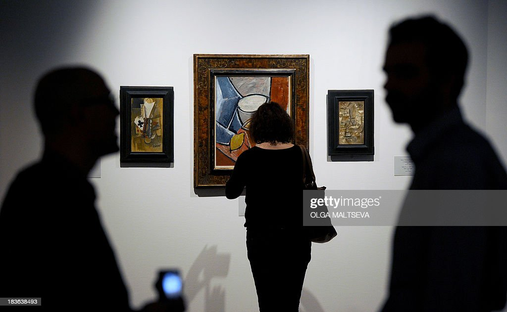 People stand in front of Pablo Picasso's paintings, (L-R) 'Playing Cards,' 'Pots and Lemon,' 'Glass and Apple,' displayed at the exhibition 'Masterpieces of Twentieth-Century Art from the Albertina Collection' in the State Hermitage Museum in St. Petersburg on October 8, 2013. More than 55 paintings of great artists of the 20th century were exhibited today in the Nicholas hall of former Czar's Winter Palace. AFP PHOTO / OLGA MALTSEVA