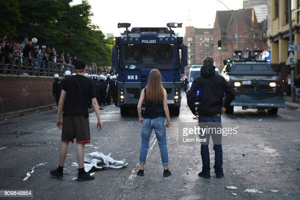 People stand in front of police vehicles during the 'Welcome to Hell' protest march on July 6 2017 in Hamburg Germany Leaders of the G20 group of...