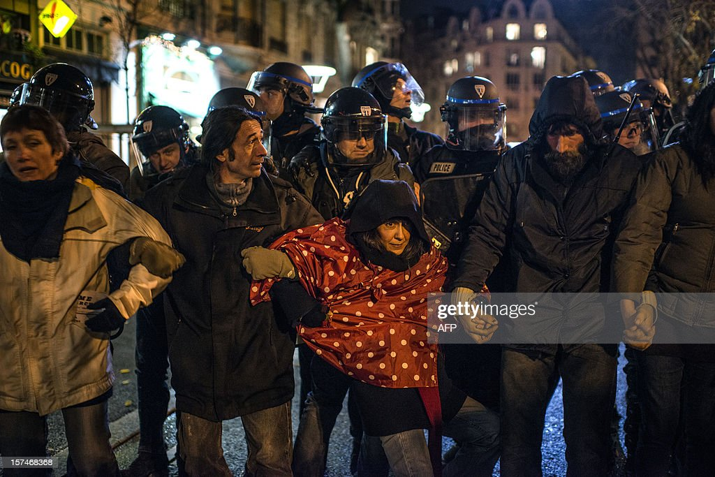 People stand in front of riot police during a demonstration against the new LGV Lyon-Turin project, on December 3, 2012 in Lyon, on the sideline of the 30th France-Italy annual summit.