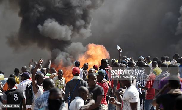 People stand in front of smoke rising from the Burkina Faso's Parliament where demonstrators set cars on fire parked in a courtyard of the Parliament...