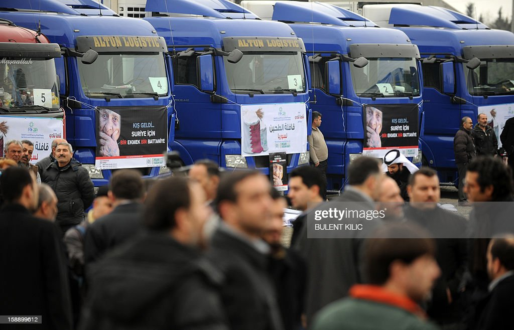 People stand in front of supply trucks of the Foundation for Human Rights and Freedoms and Humanitarian Relief (IHH) bearing placards reading ''Winter has arrived in Syria, Bread and Blankets' on January 3, 2013 in Istanbul. IHH Humanitarian Relief Foundation sent 850 tons of flour to Syria. 'Bread&Blanket for Syria' campaign is supported by nearly 200 NGOs including Union of Civil Society Organizations of the Islamic World, Independent Industrialists and Businessmen Association of Turkey (MUSIAD), Turkish Volunteer Institutions Foundation, Humanitarian Aid Foundation (IHH), Deniz Feneri Association, Cansuyu Aid Association, Yardimeli Association, Ensar Foundation, Verenel Association and Istanbul International Brotherhood and Assistance Association.